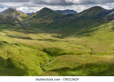 The view of a green valley in Ireland's Connemara National Park with the Twelve Bens Mountains in the background