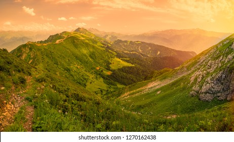 View of the Green Valley, surrounded by high mountains in the light of the sunset yellow sun.