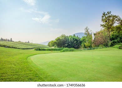 A view of the green at Zlati Gric Golf Course with trees and vineyard on a sunny day in Slovenia - Shutterstock ID 1749356636