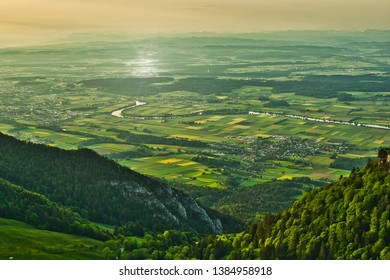 View of the green-awakening country with river and small villages seen from the mountains of the Jura shortly after sunrise.