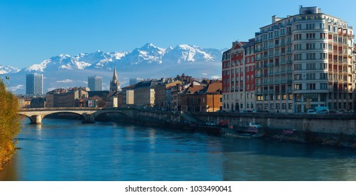 View of Grenoble with gothic spire of Saint-Andre Church against backdrop of snowy Alps in sunny day, France