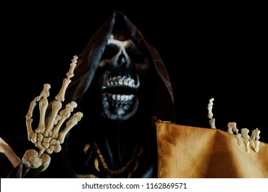 View of grim reaper show middle finger on black background. Grim Reaper, The Death. Shallow depth of field.
