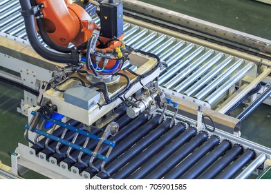 View of  gripper on industrial robot arm and roller conveyors