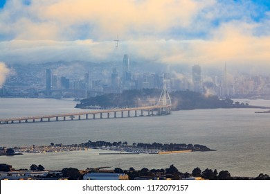 View from Grizzly Peak in the Berkeley Hills onto Bay Bridge and San Francisco with Karl the fog enveloping the city at sunset.