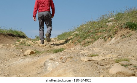 view from ground level of man walking rugged road of Nebrodi Park, Sicily