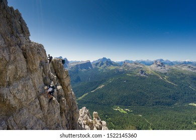 view of a group of climbers on a steep Via Ferrata with a grandiose view of the Italian Dolomites in Alta Badia behind them