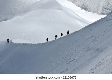 View of group hiking on slope of high Alps mountains.