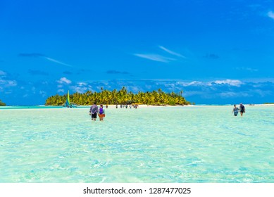 View of a group of people walking  true tranquil water, Aitutaki island, Cook Islands, South Pacific. Copy space for text