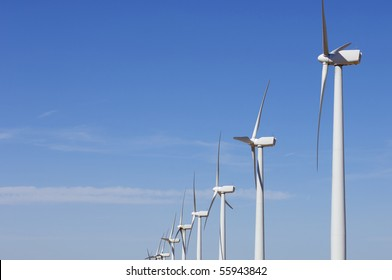 view of a group of windmills lined with blue sky