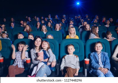 View of group of young people sitting in movie theatre, expressing emotions on their faces while watching film. Young spectators having fun, smiling. Project light source.
