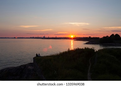 View of the Gulf of Finland at sunset of a summer day from the steep rocky shore of the island Suomenlinna Sveaborg in Finland. View from the island towards Helsinki on the horizon. Evening together