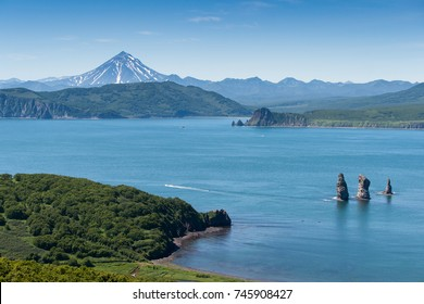 """view of the gulf of the Pacific Ocean, the cliff """"Three Brothers"""" and the hill Vilyuchinsky volcano in the background. Kamchatka Peninsula, Russia"""