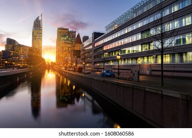 View of The Hague sunrise, early morning skyline reflected on the calm canal's water, Netherlands