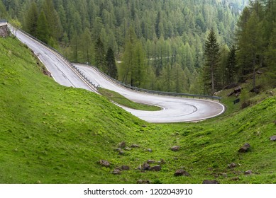 View of an Hairpin Bend along a Steep Mountain Road in the Alps on a Rainy Spring Day