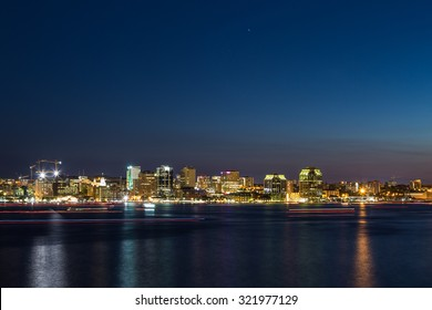 A view of Halifax Waterfront at Night. The trail of Boats can be seen in the water.