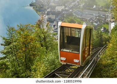 View of a Hallstatt cable car from the top station leading to a skywalk view in Austria with mist in the background.