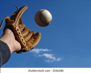 View of a hand in baseball glove reaching out to make the catch.