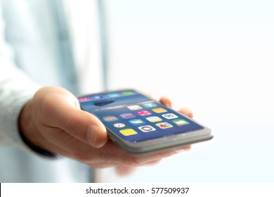 View of a Hand holding black smartphone with operating system screen