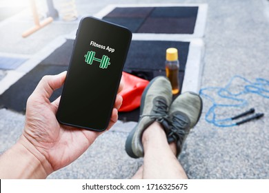 View of hand of a man holding a smart phone with fitness application at the recreational park.  Technology and sport and recreation and healthy lifestyle concept