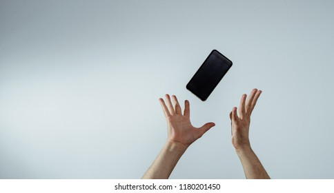 A view of the hand that tosses or catches a mobile phone. The smartphone is falling, hands are trying to catch it. The concept of communication, attempts to connect and talk.