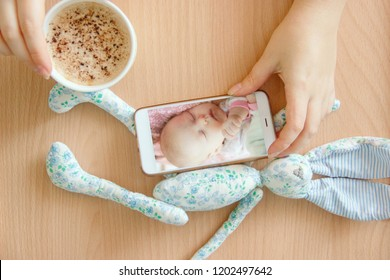 view handheld color video baby monitor. Female hands are holding a smartphone with a baby monitor app. Near hot drink and children's toy. Mother shootin her sleeping newborn baby.