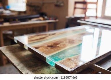 View of handmade wooden table top with epoxy resin element in lacquer on table in joinery shop
