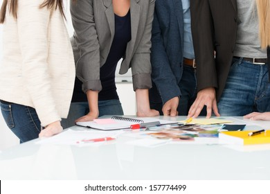 View of the hands of a group of business people selecting material for a project standing around a table on which it is displayed