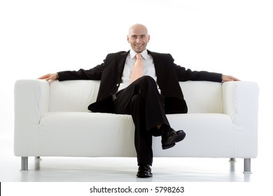 A view of a happy, satisfied businessman, relaxing on a large, white sofa.  Isolated on white background.