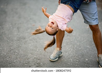 view of happy smiling little girl which her father hold upside down and swing her