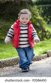View of a happy young child walking on a park.