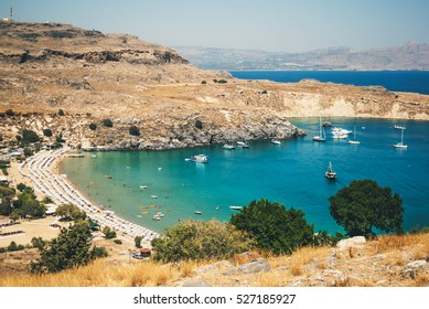 View of the harbor and the beach town of Lindos, the Acropolis, the beach with yachts and blue sea