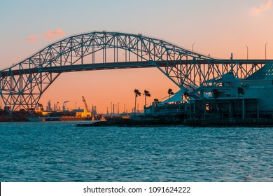 View of Harbor Bridge in Corpus Christi, Texas at sunset with oil refinery in the distance