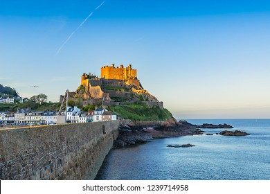 View of harbor town of Gorey with mount Orgueil Castle (Gorey Castle, built 1204 - 1450), overlooking Grouville Bay. Gorey, Jersey, Channel Islands, United Kingdom.