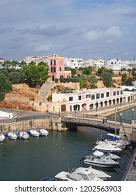 view of the harbour in ciutadella menorca with moored boats and surrounding buildings in blue summer sunlight