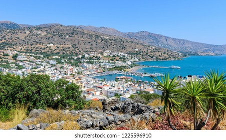 A view of the harbour and town of Elounda from a hillside. Palm trees and a stone wall are in the foreground with the harbour below and surrounding hills.