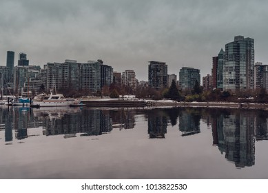 View to harbour and Vancouver (BC, Canada) city skyscrapers with reflections in the water on an overcast winter day.