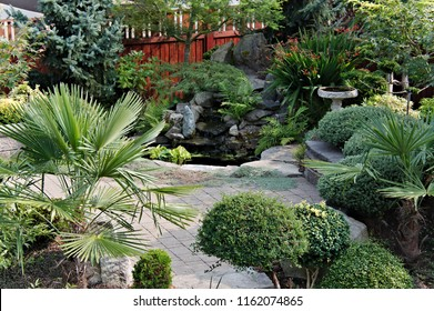 View of hardscape area paver deck retaining wall incorporated pond with waterfall part of landscape design elements background