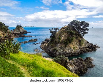 View of the Hauraki Gulf sea, taken from the Owhanake Coastal Track on Waiheke Island, New Zealand on a cloudy day. With hills and trees.