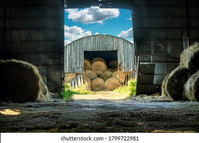 View of the hay bales being stored in an old wooden barn from the another hay barn in late summer or early autumn sunny evening. Rural scene