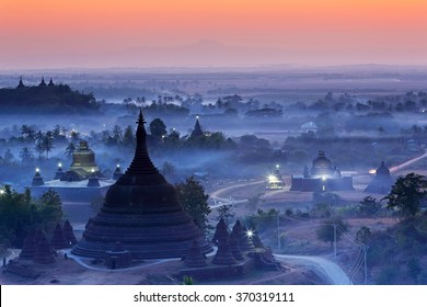 View from hazy sunset over silhouette Ratanabon Paya in Mrauk-U, Myanmar.