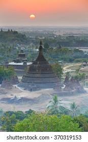 View from hazy sunset over silhouette Ratanabon Paya in Mrauk-U, Myanmar.