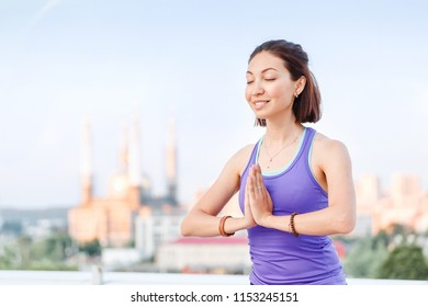 View of a healthy young sport woman practicing yoga sitting in lotos asana pose while meditating outdoors on the roof top against blue sky