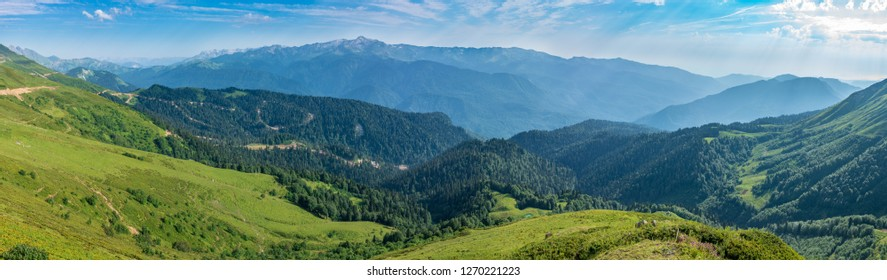 The view from the height of the green mountain valley with a cable car, surrounded by high mountains. Snow-capped mountain peaks on the horizon. Krasnaya Polyana, Sochi, Caucasus, Russia.