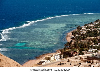 View from height on Dahab beach and coral reef. Blue sea with surf line.