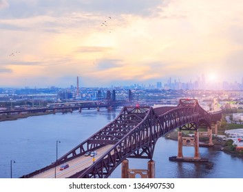 The view from the heights of the evening city of New York. View of the bridges and suburbs of New York at sunset.