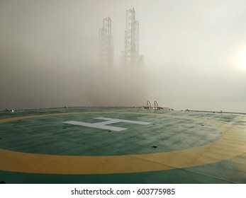 View of helicopter deck or helipad with thick morning fog during sunrise and noise background.