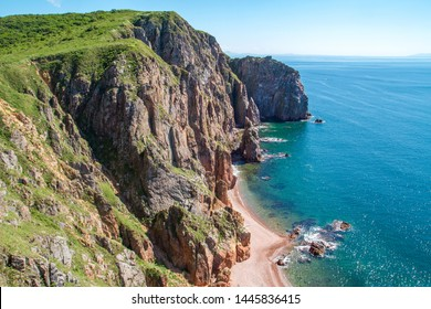 The view from the high cliff on the sandy beach of the island of Shkot. The southern part of the island Russky. Vladivostok. Sea of Japan. Travel by Russia. Russian nature at summer.