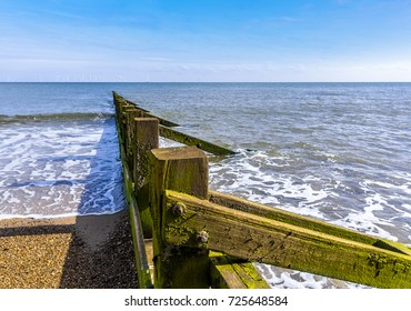 A view of the high and low sides of sea defense Groynes on Skegness beach with a wind farm  just visible on the horizon in summer.