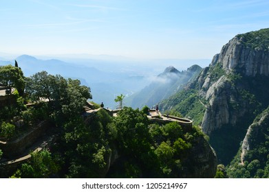 View from a high mountain platform on the mountains with trees, valley, observation place on a sunny day with haze in the distance.
