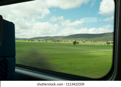 View from high speed train window in motion of countryside and sky on sunny warm Spring day in Spain